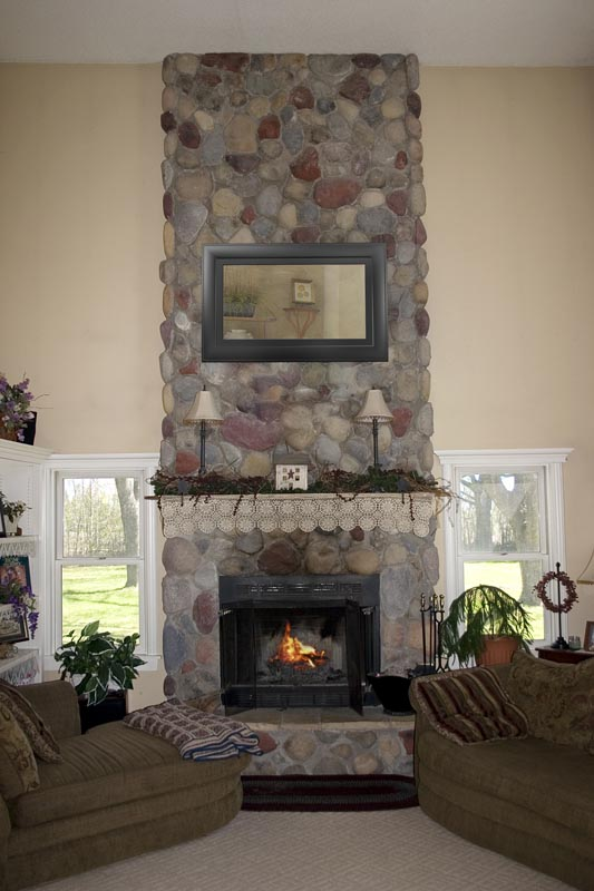 Stone fireplace with mirror television discreetly hidden