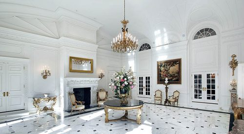 White grand foyer with fireplace and chairs